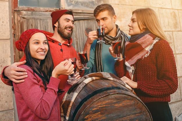 Uśmiechnięci europejczycy i europejczycy podczas sesji zdjęciowej. faceci udający przyjaciół na festynie w studiu z kieliszkami i grzanym winem na pierwszym planie.