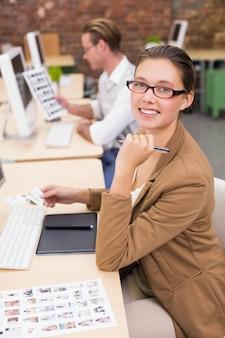 Uśmiechnięci fotografia redaktorzy używa komputery w biurze