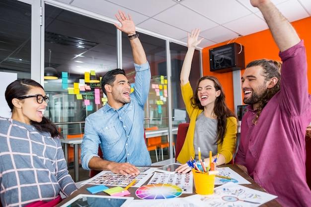 Uśmiechnięci graficy z rękami uniesionymi do góry podczas spotkania