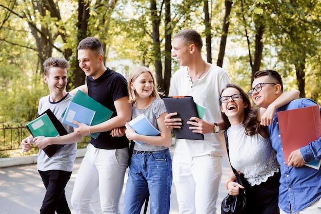 Uśmiechnięci i roześmiani studenci spacerujący w parku podczas przerwy, opowiadający dowcipy