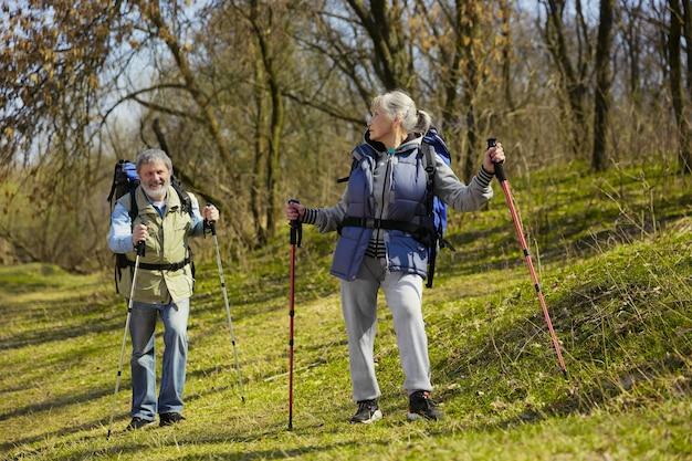 Uśmiechnięci i szczęśliwi razem. starsza rodzina para mężczyzny i kobiety w stroju turystycznym spaceru na zielonym trawniku w słoneczny dzień w pobliżu potoku. pojęcie turystyki, zdrowego stylu życia, relaksu i wspólnoty.