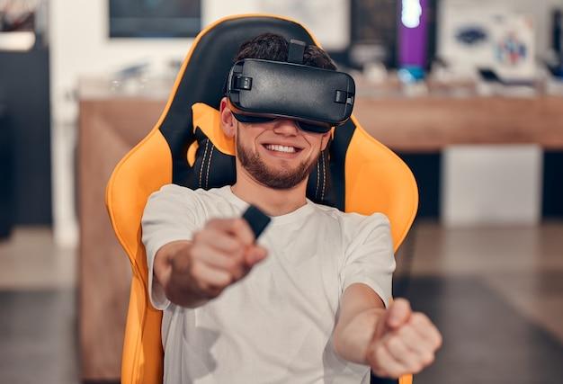 Uśmiechnięci kaukascy mężczyźni w białej koszulce wypróbowują technologię wirtualnej rzeczywistości, siedząc na krześle w sklepie technicznym.