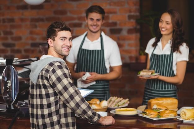 Uśmiechnięci kelnerzy i klient patrzeje kamerę