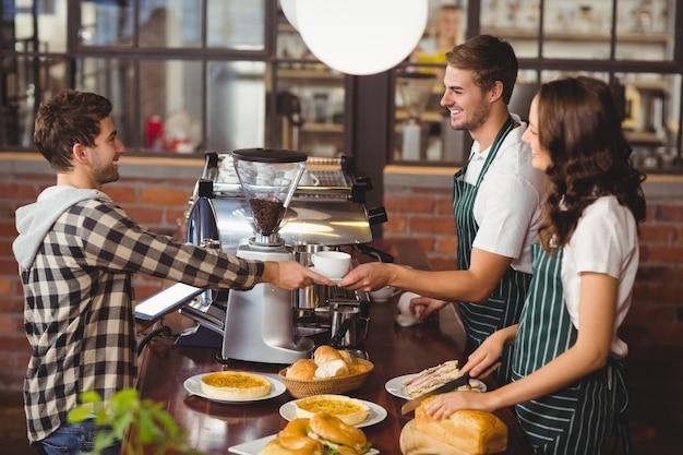 Uśmiechnięci kelnerzy obsługują klienta