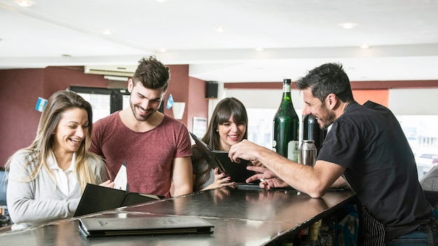 Uśmiechnięci klienci przy kontuarem baru