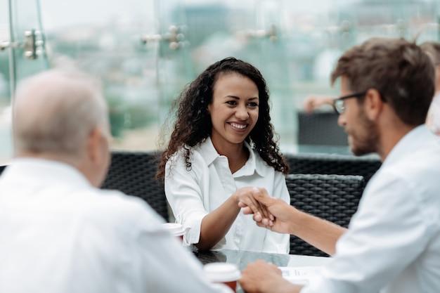 Uśmiechnięci koledzy biznesowi ściskający dłonie z bliska