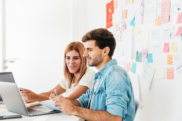 Uśmiechnięci koledzy patrzeje laptop w miejscu pracy