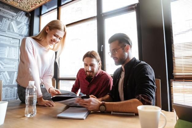 Uśmiechnięci koledzy siedzi w biurze i coworking