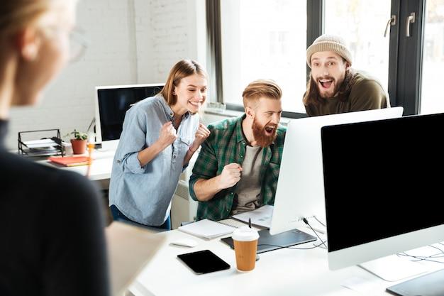 Uśmiechnięci koledzy w biurze opowiada