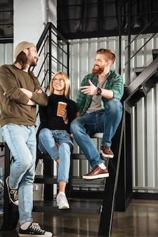 Uśmiechnięci koledzy w biurze rozmawiają ze sobą