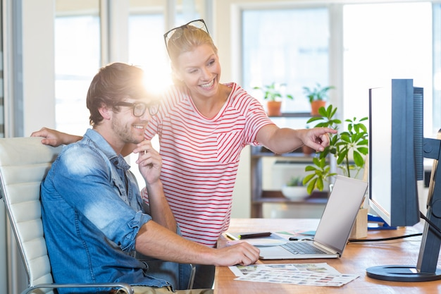 Uśmiechnięci koledzy wskazuje przy laptopem