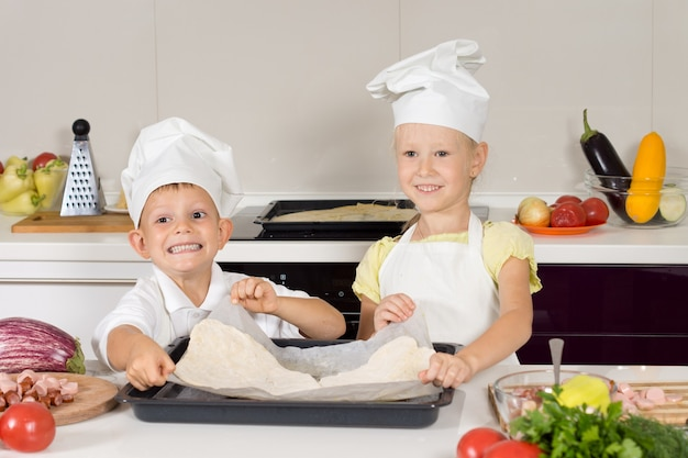 Uśmiechnięci kucharze przygotowujący pizzę domowej roboty