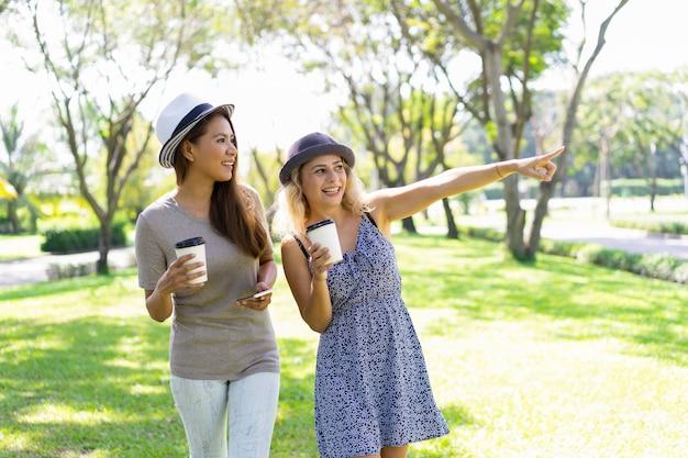 Uśmiechnięci ładni młodzi żeńscy przyjaciele chodzi w lato parku