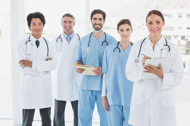 Uśmiechnięci lekarze wszyscy stojąc razem