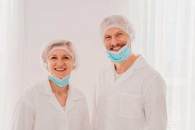 Uśmiechnięci lekarze z maską na twarz chętnie pracują przeciwko covid-19