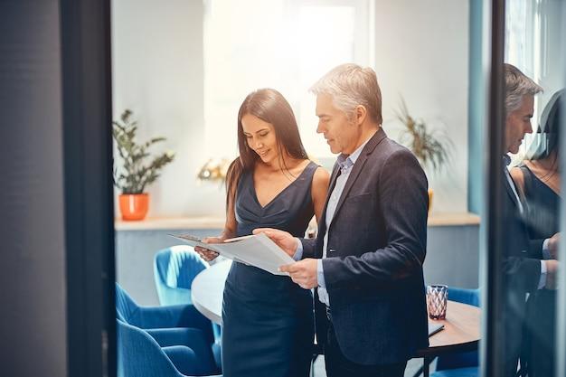 Uśmiechnięci ludzie biznesu czytający opinie o swojej firmie