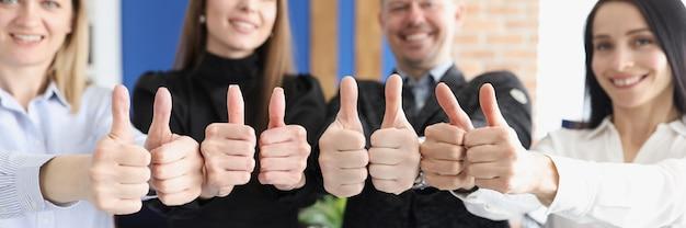 Uśmiechnięci ludzie biznesu pokazują kciuki do góry gestem stoją w biurze