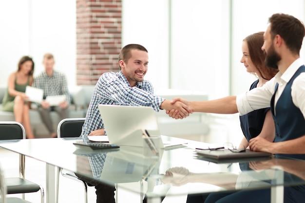 Uśmiechnięci ludzie biznesu, ściskając ręce na biurku