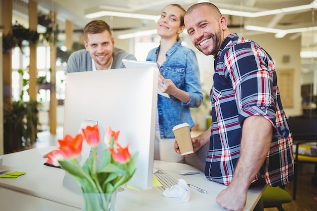 Uśmiechnięci ludzie biznesu stoi przy biurkiem w kreatywnie biurze
