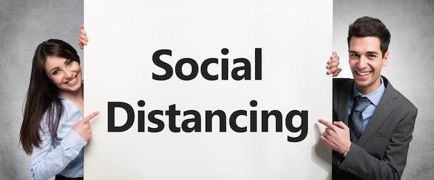 Uśmiechnięci ludzie biznesu trzyma białą deskę z teksta socjalny dystansowaniem