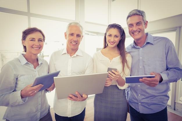 Uśmiechnięci ludzie biznesu z urządzeniami elektronicznymi