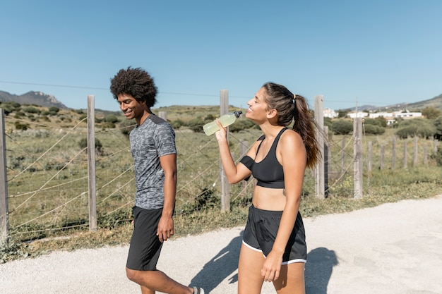 Uśmiechnięci ludzie chodzi podczas gdy kobiety woda pitna