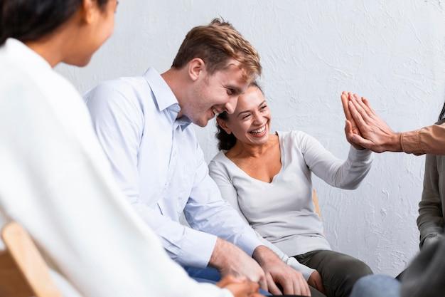 Uśmiechnięci ludzie na sesji terapii grupowej przybijają sobie piątki