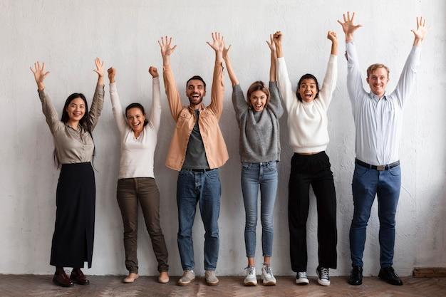 Uśmiechnięci ludzie podnoszą ręce na sesji terapii grupowej