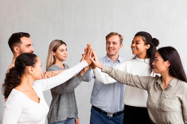 Uśmiechnięci ludzie przybijają sobie piątki na sesji terapii grupowej