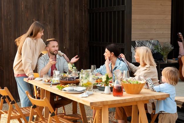 Uśmiechnięci ludzie siedzący przy stole, średni strzał