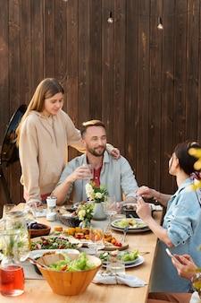 Uśmiechnięci ludzie siedzący przy stole
