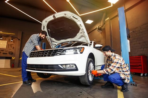 Uśmiechnięci mechanicy naprawiający nowoczesny samochód w warsztacie