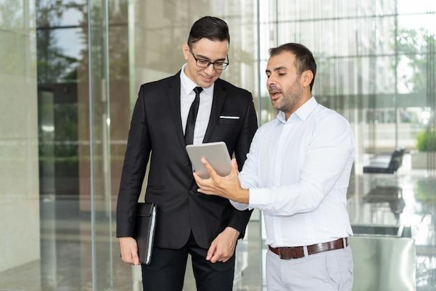 Uśmiechnięci menedżerowie firmy it omawiający nowy produkt