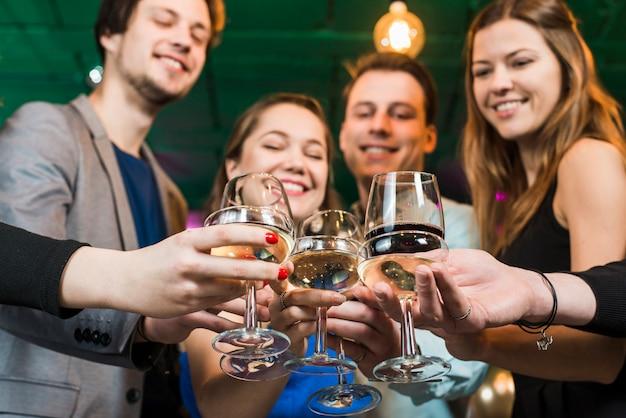 Uśmiechnięci męscy i żeńscy przyjaciele wznosi toast koktajle w przyjęciu przy barem