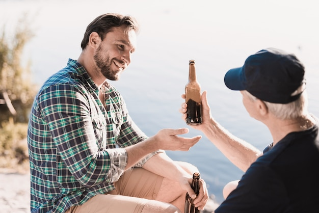 Uśmiechnięci mężczyzna pije piwo blisko rzeki w lecie.