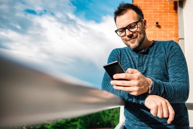 Uśmiechnięci mężczyzna pisać na maszynie wiadomość tekstową