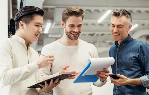Uśmiechnięci mężczyźni rozmawiają o projekcie w pracy