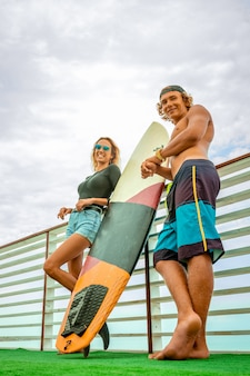 Uśmiechnięci młodzi aktywni para surfingowowie relaksuje na plaży po sporta z surfboard. zdrowy tryb życia. sporty wodne ekstremalne