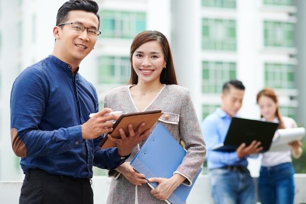 Uśmiechnięci młodzi azjatyccy biznesmeni omawiania dokumentu na komputerze typu tablet i uśmiechnięty