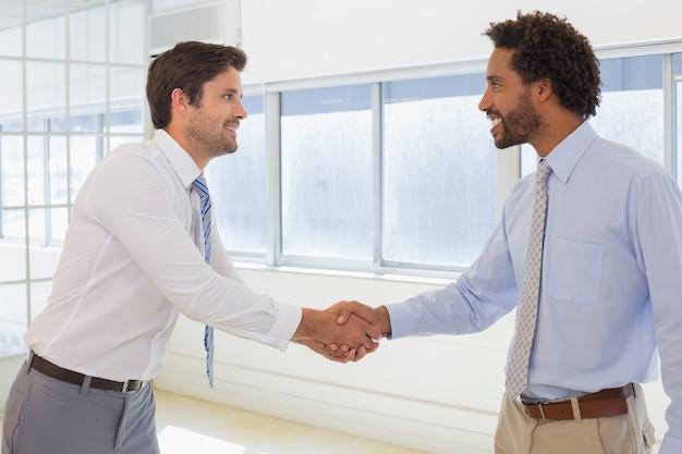 Uśmiechnięci młodzi biznesmeni trząść ręki w biurze