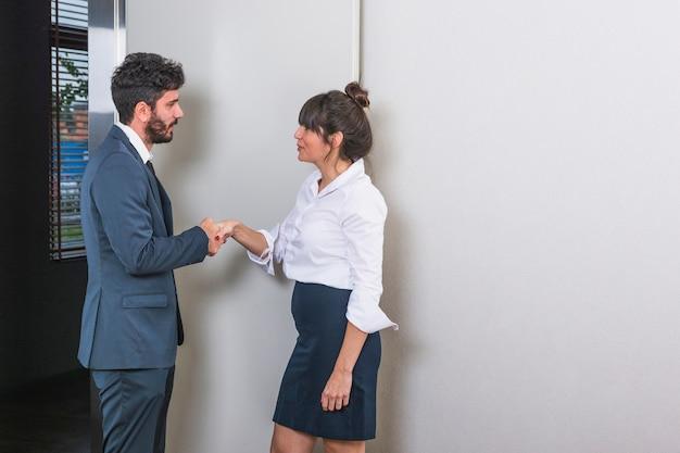 Uśmiechnięci młodzi biznesmeni trząść ręki