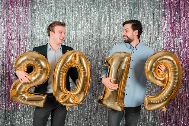 Uśmiechnięci młodzi faceci z złocistymi balonami liczby