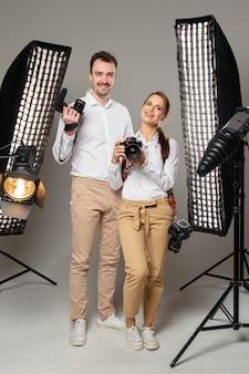 Uśmiechnięci młodzi fachowi fotografowie pozuje w studiu