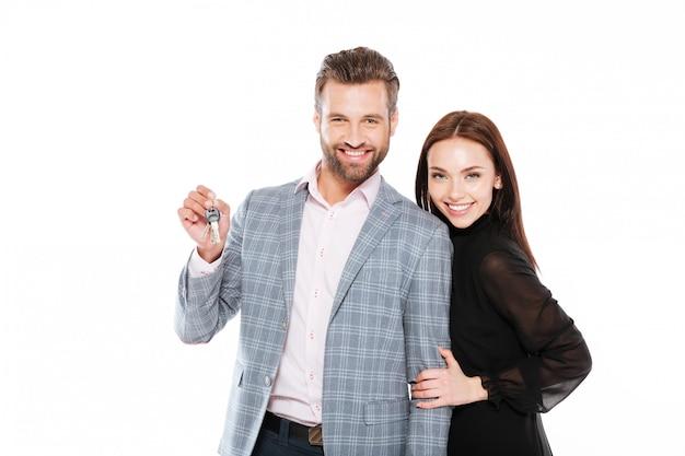 Uśmiechnięci młodzi kochający pary mienia klucze.