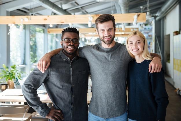 Uśmiechnięci młodzi koledzy stoi w biurze