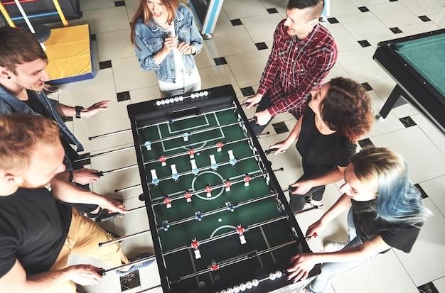 Uśmiechnięci młodzi ludzie bawić się stołowego futbol podczas gdy indoors