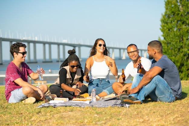 Uśmiechnięci młodzi ludzie ma pinkin w parku. uśmiechnięci przyjaciele siedzi na kocu i pije piwo. wolny czas