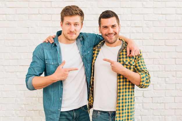 Uśmiechnięci młodzi mężczyźni z ramionami, wskazując palcami na siebie