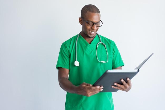 Uśmiechnięci młodzi ogólnego lekarza praktykującego czytania dokumenty w falcówce.
