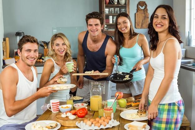 Uśmiechnięci młodzi przyjaciele ma śniadanie przy stołem
